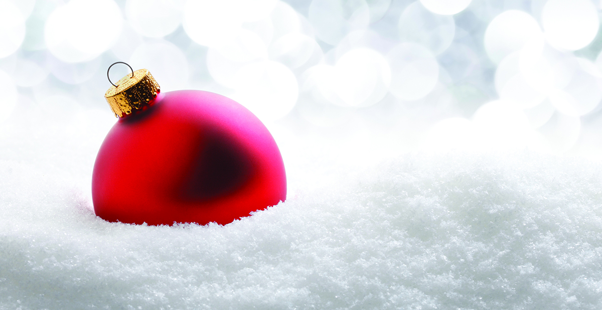 One red Christmas ornament resting in softly fallen snow. The red ornament is in front of white blurred lights..  There is room for text.